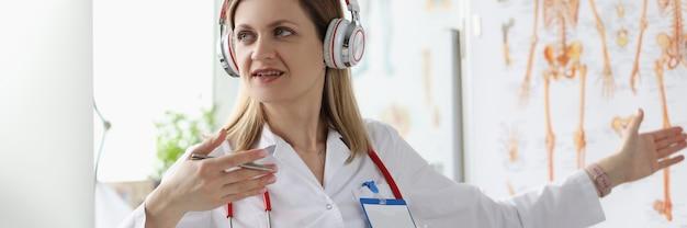 헤드폰을 쓴 여자 의사가 의학 온라인 교육을 실시합니다.