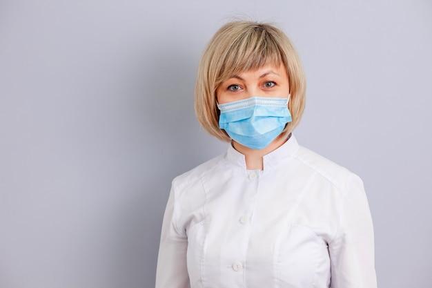 灰色の背景にマスクの女医師