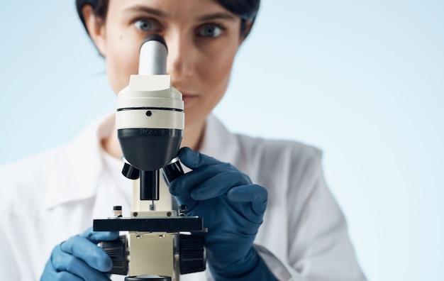 의료 장갑 및 테이블 전문 실험실 현미경에 여자 의사.