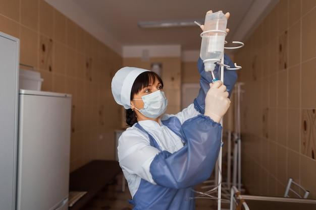 病棟にいる手に、保護マスクをはめた医療用手袋をはめた女医が立って点滴をしている。患者の世話をする看護師