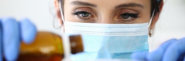 의료 보호 마스크에 여자 의사는 숟가락 초상화에 항아리에서 약을 따른다. 개념 기침 시럽의 의심스러운 효과.