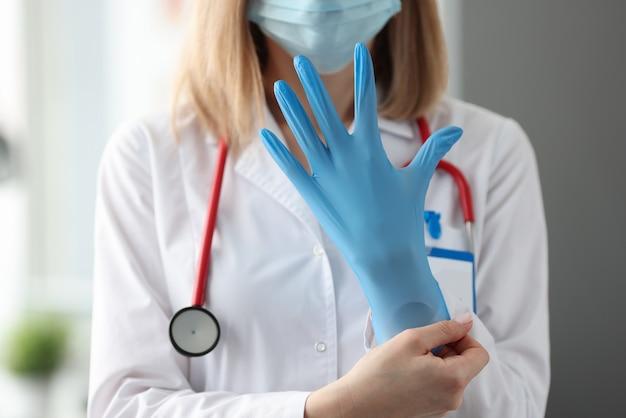 Женщина-врач в защитной медицинской маске надевает резиновую перчатку. санитарные нормы в концепции медицины