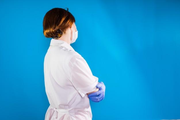 青い手袋を着用した白い白衣の女医。側面図。青い背景に分離