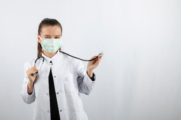 의료 마스크를 착용하고 청진기를 들고 흰색 제복을 입은 여자 의사