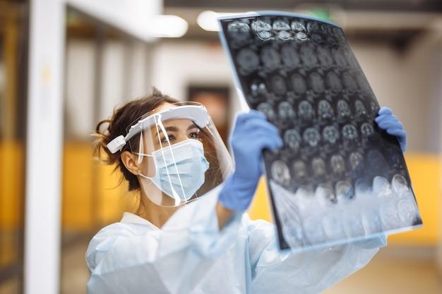 Женщина-врач проверяет рентгеновское изображение мрт головного мозга пациента в больнице. женский медицинский работник в защитной маске и белом халате в коридоре больницы. концепция здоровья и медицины.