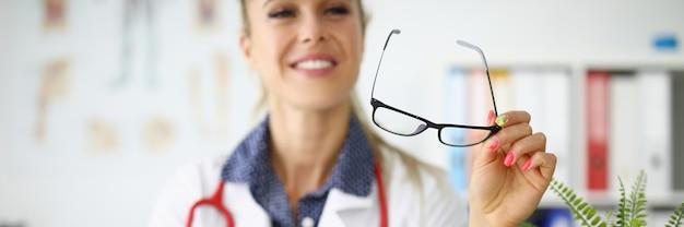 Женщина-врач сидит за столом, улыбаясь и держа в руках очки