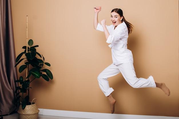 茶色の背景に注射器でジャンプする女医師
