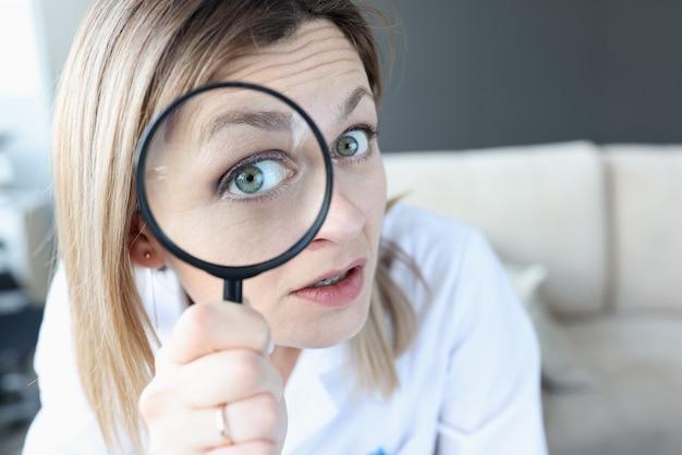 虫眼鏡のクローズアップを通して見ている女医。腫瘍学的検索の概念