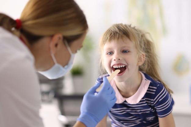 保護医療マスクとゴム手袋の女医小児科医は、小さな女の子の木製のスパチュラの肖像画の喉を調べます