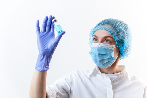 Woman doctor in protective gloves mask holding bottle with injection vaccine