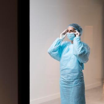 Женщина-врач надевает маску для лица