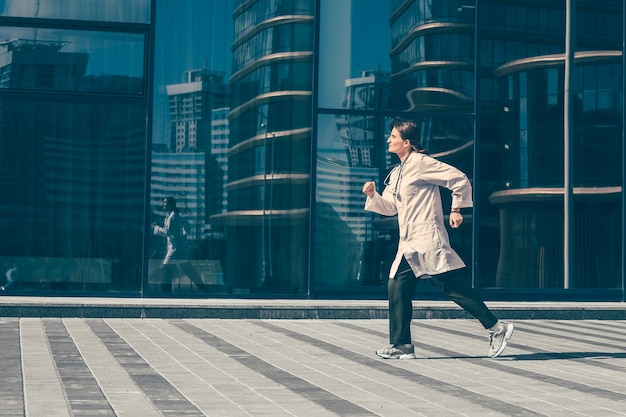 Woman doctor runs down a city street. photo with a copy-space.
