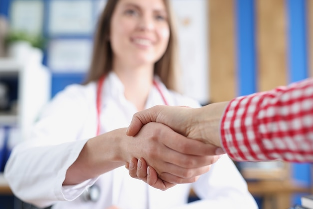 Woman doctor shaking hand of patient in clinic closeup
