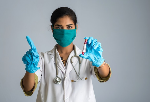Woman doctor showing signs with holding a test tube with blood sample for coronavirus or 2019-ncov analyzing.