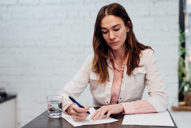 女医は机に座ってペンで一枚の紙に書く。