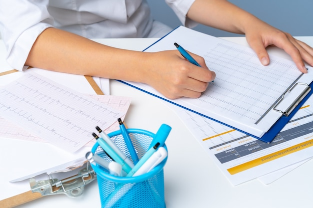 Woman doctor taking notes on clipboard while sitting at her table in office