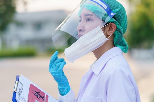 Женщина-врач снимает маску и держит отчет пациента