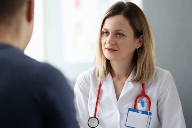 Woman doctor talking to patient in clinic. psychological help concept