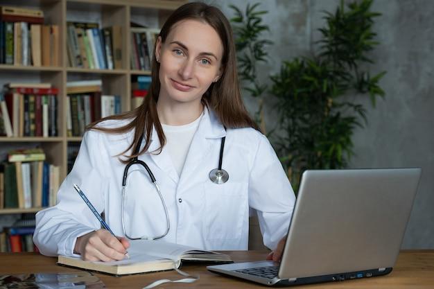 Женщина-врач, использующая на своем портативном компьютере в медицинском кабинете