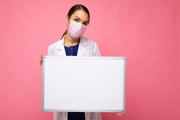 白い医療コートと空白のボードを保持しているマスクを身に着けている女医師