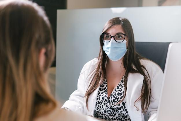 フェイスマスクを着用し、彼女のオフィスで患者と話している女医