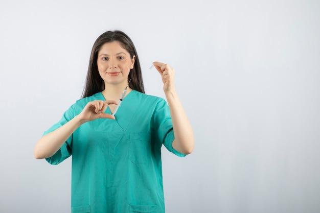 Medico della donna che indossa la siringa verde della tenuta dell'uniforme su bianco.