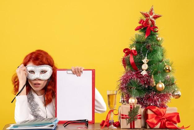 Donna medico che indossa una maschera intorno all'albero di natale e regali su giallo