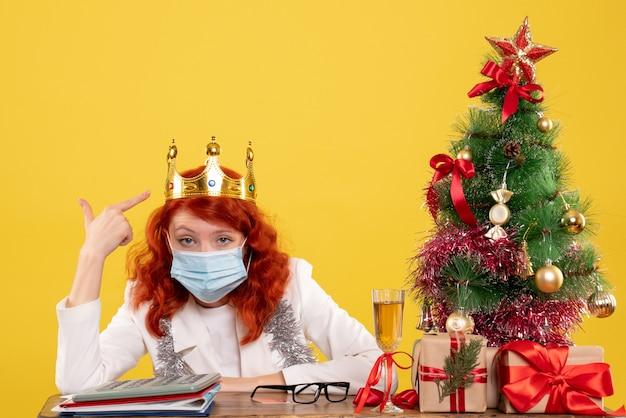 Donna medico che indossa una maschera con corona in testa su giallo