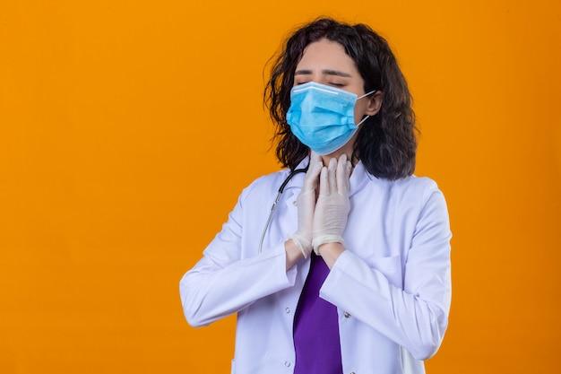 Женщина-врач в белом халате со стетоскопом в медицинской защитной маске выглядит нездоровой, трогает шею и страдает от боли, стоя на изолированном апельсине