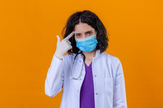 分離された黄色の上に立って深刻な表情で考えに懸命に集中して指で寺院を指している医療用防護マスクで聴診器で白いコートを着ている女性医師