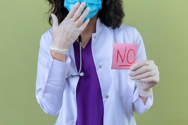 Donna medico che indossa camice bianco con stetoscopio in maschera protettiva medica tenendo carta promemoria senza parola che sembra sorpreso sul verde isolato