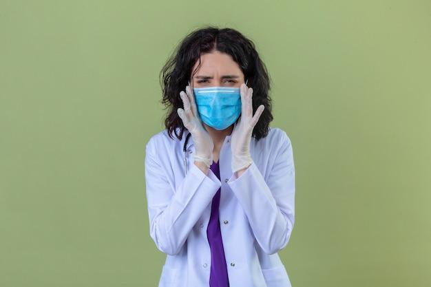 Donna medico che indossa camice bianco con uno stetoscopio in maschera protettiva medica cercando malessere toccando templi con le mani che hanno forte mal di testa in piedi sul verde isolato