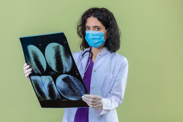 Woman doctor wearing white coat with stethoscope in medical protective mask standing with x-ray of lungs with serious face on isolated green