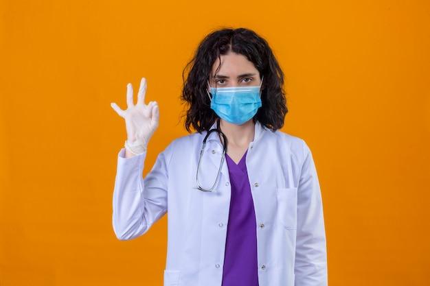 Donna medico che indossa camice bianco con stetoscopio in maschera protettiva medica con viso serio facendo segno ok in piedi su arancione isolato