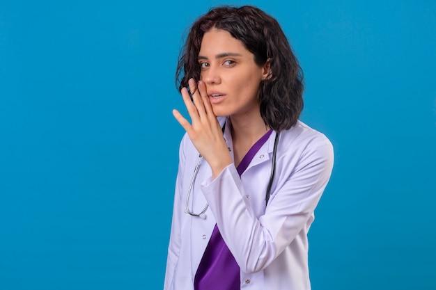 Женщина-врач в белом халате со стетоскопом, стоя с рукой возле рта, рассказывая секрет на изолированном синем