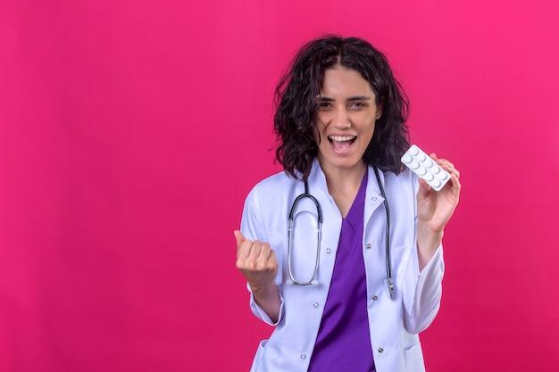 Donna dottore, il portare, camice bianco, con, stetoscopio, standing, con, blister, di, pillole, in, mano, gioia, suo, successo, e, vittoria, stringendo mano, con, gioia