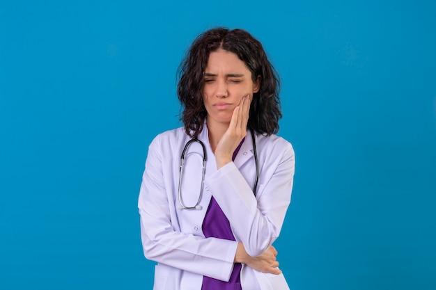 격리 된 파란색에 양식 치통을 겪고 뺨에 손으로 청진 서와 흰색 코트를 입고 여자 의사