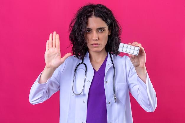Женщина-врач в белом халате со стетоскопом стоит с открытой рукой, делая жест стоп и держа блистер с таблетками в другой руке на изолированном розовом