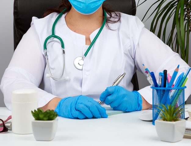 Woman doctor in a white coat, sterile medical gloves writes a pr