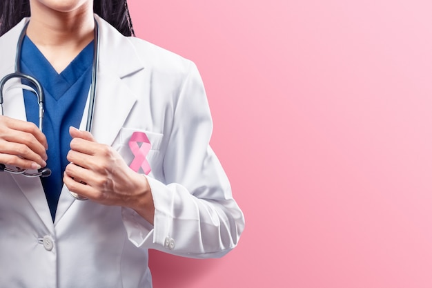 A woman doctor in a white lab coat holding a stethoscope on her hands with pink ribbon over pink background