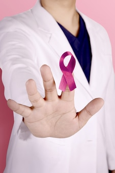 A woman doctor in a white lab coat with stop gesture hand and showing pink ribbon on her finger