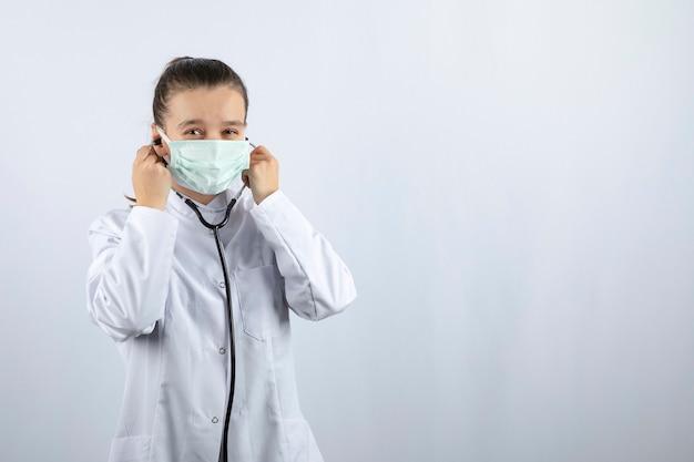 Medico donna in uniforme bianca che indossa una maschera medica e tiene in mano uno stetoscopio