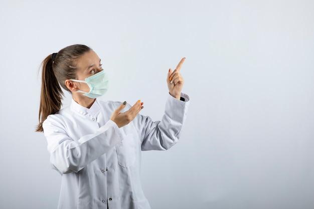 Medico donna in uniforme bianca che indossa una maschera medica e indicando via