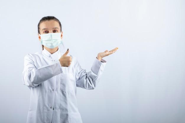 Medico donna in uniforme bianca che indossa una maschera medica che mostra un pollice in su