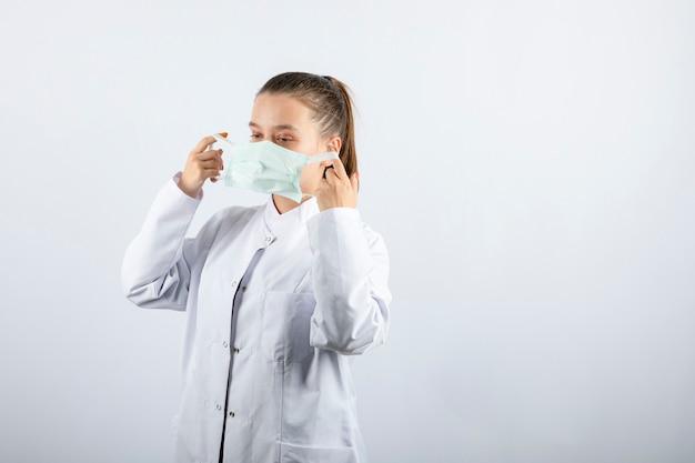 Medico donna in uniforme bianca che indossa una maschera medica