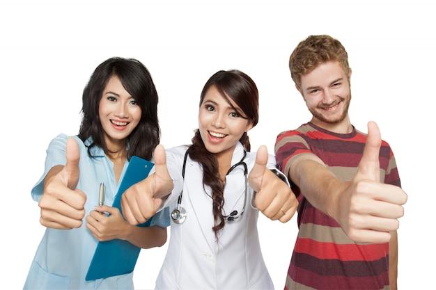 Женщина-врач с помощником и пациентом, давая пальцы