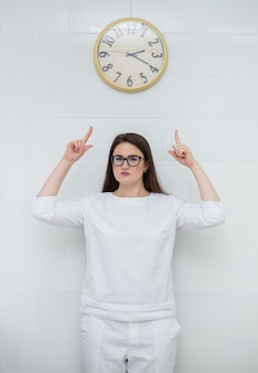 Woman doctor with brown hair in a white medical gown stands and points at the clock face