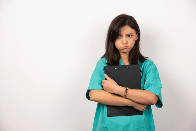 白い背景に息を止めてクリップボードを持つ女医師。高品質の写真