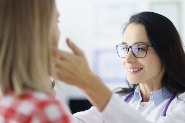 クリニックで患者の顎下リンパ節を検査する眼鏡をかけた女性医師。悪性疾患の概念の診断