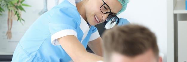クリニックで若い男性のお尻の皮膚の発疹を調べる眼鏡をかけた女医